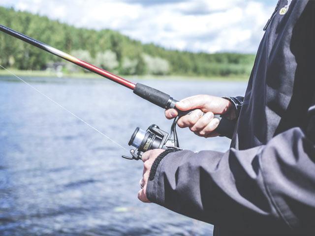 Mann fisker ved innsjø