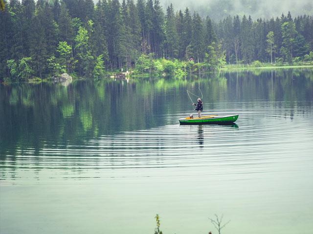 Mann fisker fra båt