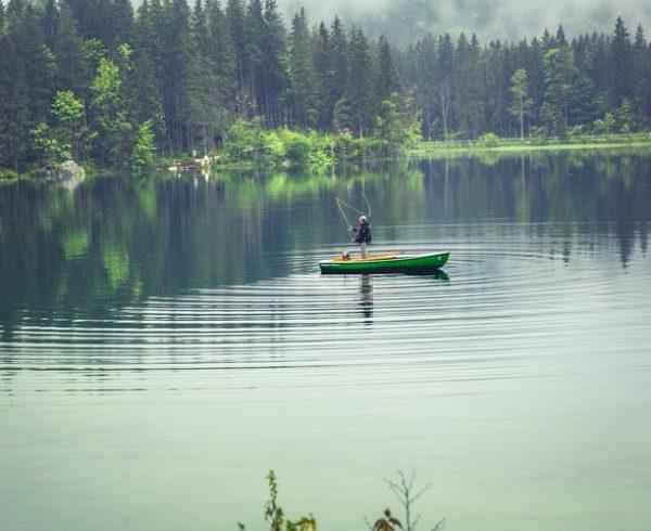 Mann i båt som fisker.